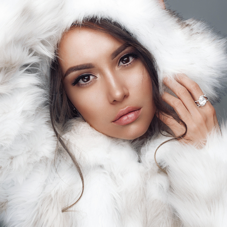 Fashion studio portrait of beautiful lady in white fur coat and fur hat. Winter beauty in luxury. Fashion fur. Beautiful woman in luxury fur coat. Fashion model posing in eco-fur coat and eco-fur hat Stockfoto