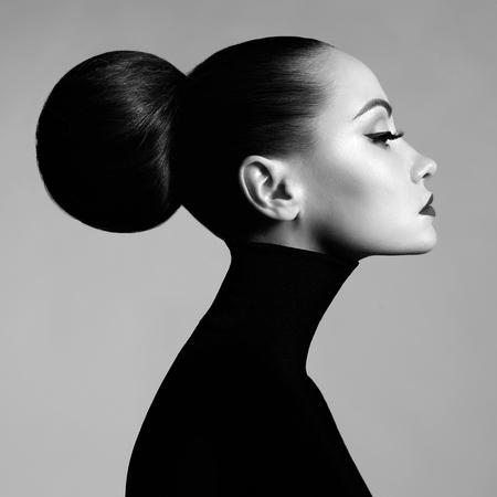 Retrato preto e branco do estúdio da arte da forma da mulher elegante bonita na gola alta preta. O cabelo é coletado em feixe de luz. Estilo de balé elegante