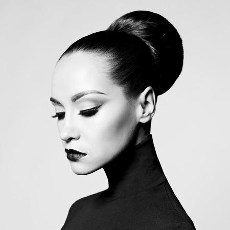 Retrato preto e branco do estúdio da arte da forma da mulher elegante bonita na gola alta preta. O cabelo é coletado em feixe de luz. Estilo de balé elegante Foto de archivo