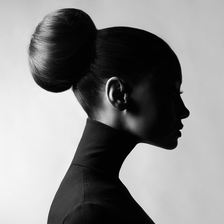 Black and white fashion art studio portrait of beautiful elegant woman in black turtleneck. Hair is collected in high beam. Elegant ballet style
