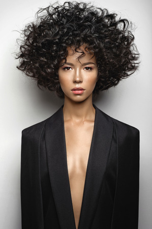 Fashion studio portrait of beautiful woman in black cape with afro curls hairstyle. Fashion and beauty