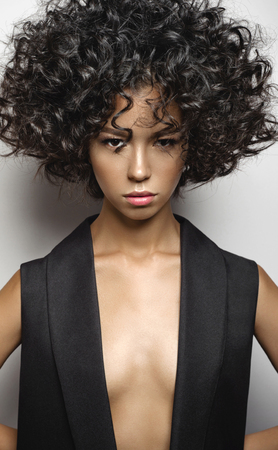 Fashion studio portrait of beautiful woman in black vest with afro curls hairstyle. Fashion and beauty