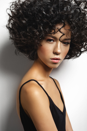 Fashion studio portrait of beautiful woman in black dress with afro curls hairstyle. Fashion and beauty 스톡 콘텐츠