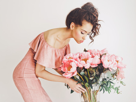 Lifestyle photo of beautiful young woman with pink peonies. Bouquet as gift. Emotions of happiness and joy. Valentines day. Mothers day Stock Photo