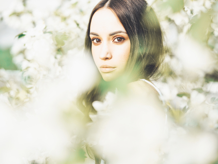 Outdoor fashion photo of beautiful young woman surrounded by flowers of apple-tree. Spring blossom. Summer vibes Stock Photo