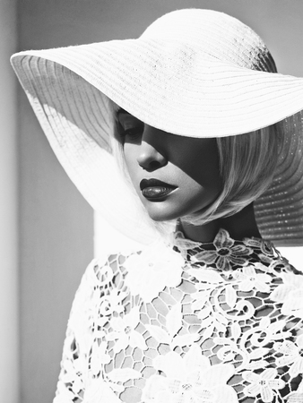 Black and white outdoor fashion photo of young beautiful lady in white hat. Summer Beach travel. Summer vibes
