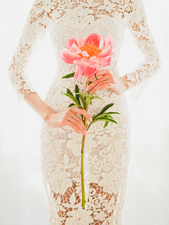 Lifestyle fashion photo of beautiful young woman in white lace dress with pink peony. Holidays and Events. Wedding. Valentines Day. Spring blossom. Summer season. Stock Photo