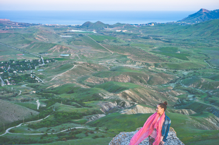 Outdoor lifestyle photo of young happy woman walking on mountain. Travel background. Tourism