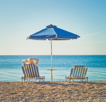 Woman on southern beach resting in a chaise-longue under an umbrella. Summer travel. Beach vibes