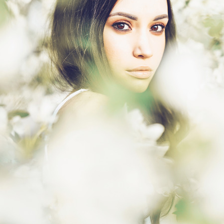 Outdoor fashion photo of beautiful young woman surrounded by flowers of apple-tree. Spring blossom. Summer vibes Stockfoto