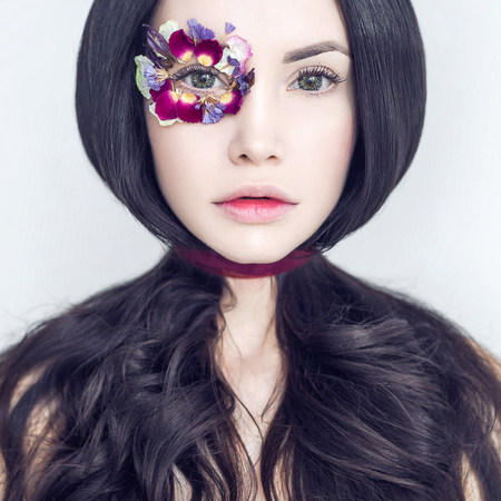 Art fashion portrait of beautiful woman with bright makeup decorated with flowers. Fantasy girl portrait. Summer fairy portrait. Long hair