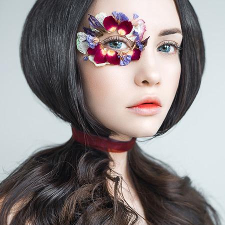 花で飾られた明るいメイクで美しい女性のアートファッションの肖像画。ファンタジーの女の子の肖像画。夏の妖精の肖像画。長い髪