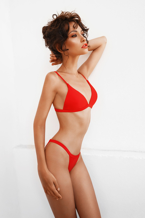 Lifestyle fashion photo of beautiful graceful woman in red bikini. Spring Summer. Beach summer vibes. Travel season