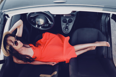Outdoor lifestyle photo of beautiful stylish woman in car cabriolet. Holiday and travel. Summer trip. Freedom, youth and carefree Stock Photo