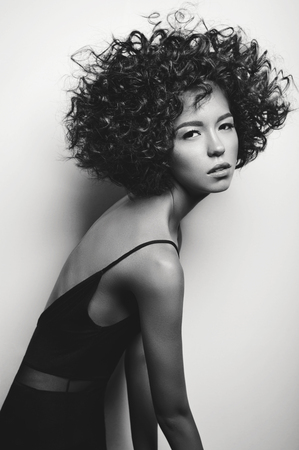 Black and white fashion studio portrait of beautiful woman in black dress with afro curls hairstyle. Fashion and beauty