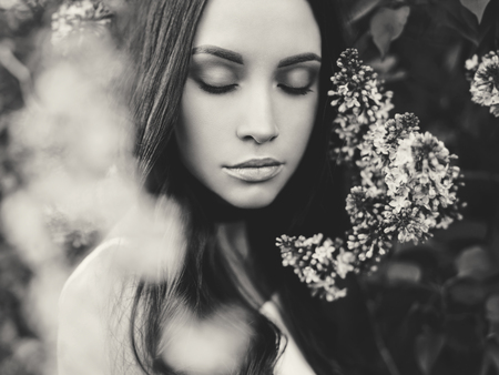 Black and white outdoor fashion photo of beautiful young woman surrounded by flowers of lilac. Spring blossom Zdjęcie Seryjne