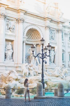 Beautiful woman in white dress take a photo of Trevi Fountain, Rome, Italy. Happy woman enjoy italian vacation. Holiday in Europe Stockfoto