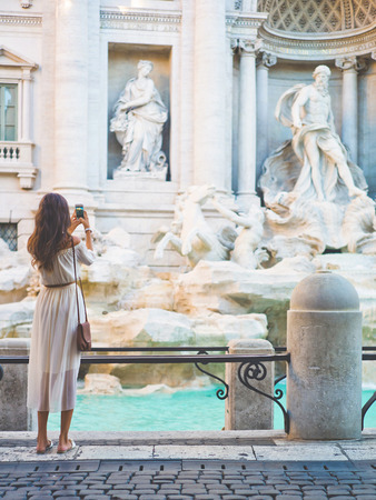 Beautiful woman in white dress take a photo of Trevi Fountain, Rome, Italy. Happy woman enjoy italian vacation. Holiday in Europe. Stock Photo