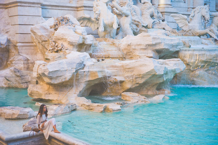 Beautiful woman in white dress sitting in front of Trevi Fountain, Rome, Italy. Happy woman enjoy italian vacation. Holiday in Europe. Stock Photo