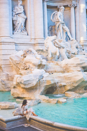 Beautiful woman in white dress sitting in front of Trevi Fountain, Rome, Italy. Happy woman enjoy italian vacation. Holiday in Europe. Stockfoto