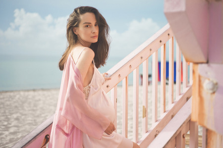 Outdoor atmospheric lifestyle portrait of beautiful pregnant woman in pink dress on pink lifeguard tower. Beautiful morning. Sunrise on the beach. Beauty and fashion. Pink aesthetic Stock Photo