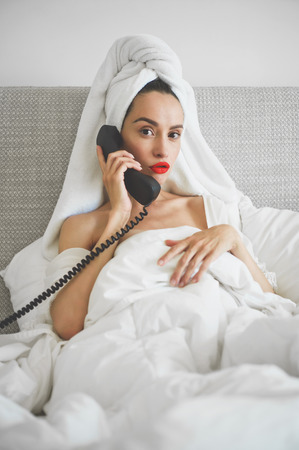 Lifestyle portrait of beautiful  woman caller in bed. Beautiful morning. Beauty and health