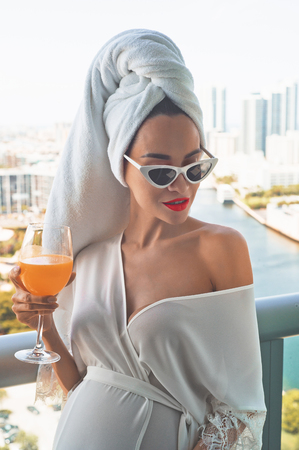 Young beautiful pregnant woman on balcony with glass of orange juice. Beautiful morning. Fashion and beauty