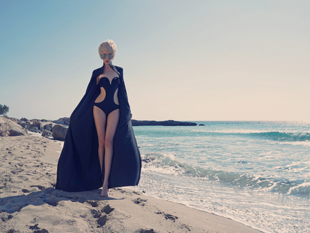 Outdoor fashion photo of beautiful slender woman in black tunic on the beach