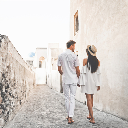 Outdoor lifestyle photo of happy young couple in white european town. Walking on Santorini island 写真素材