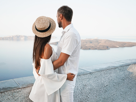 Outdoor lifestyle photo of happy young couple in white european town. Walking on Santorini island Stok Fotoğraf