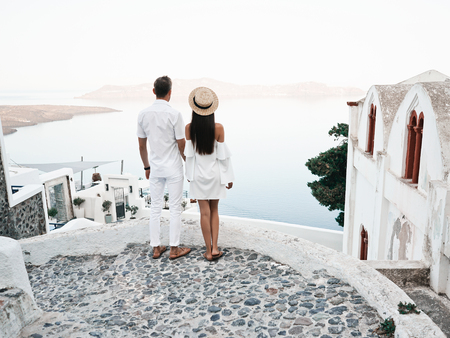 Outdoor lifestyle photo of happy young couple in white european town. Walking on Santorini island Imagens