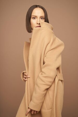 Fashion studio photo of young beautiful lady in beige coat on beige background. Total beige. Fashion look book. Warm Autumn. Warm Spring Stock Photo