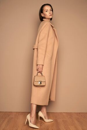 Fashion studio photo of young beautiful lady in beige coat with little handbag on beige background. Total beige. Fashion look book. Warm Autumn. Warm Spring Banco de Imagens