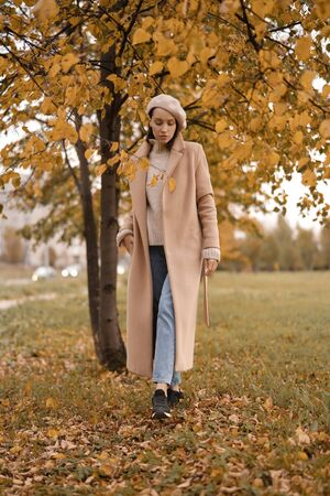 Outdoor fashion photo of young beautiful lady in beige coat, knite sweater and blue jeans in autumn landscape. Warm autumn