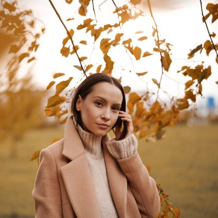 Outdoor fashion photo of young beautiful lady in beige coat surrounded autumn leaves