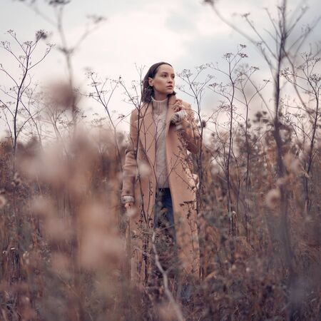 Outdoor fashion photo of young beautiful lady in autumn landscape with dry flowers. Knitted sweater, beige coat. Warm Autumn. Warm Spring Banco de Imagens