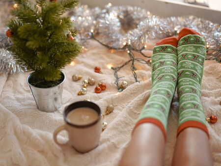 Feet in christmas socks near the Christmas tree. Woman sitting at the blanket, drinks hot beverage and relaxes warming up their feet in woollen socks. Winter and Christmas holidays concept Banco de Imagens