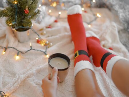 Feet in Santa's socks near the Christmas tree. Woman sitting at the blanket, drinks hot beverage and relaxes  warming up their feet in woollen socks. Winter and Christmas holidays concept