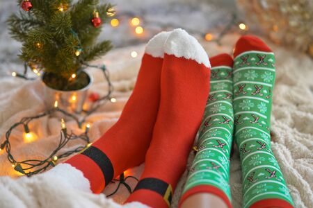 Feet in christmas socks near the Christmas tree. Couple sitting at the blanket, relaxes warming up their feet in woollen socks. Winter and Christmas holidays concept
