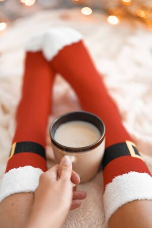 Lifestyle home photo of feet in Santa's socks near the Christmas tree. Woman sitting at the blanket, drinks hot beverage and relaxes  warming up their feet in woollen socks. Winter and Christmas holidays concept Banco de Imagens - 137874892