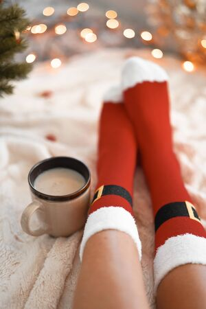 Lifestyle home photo of feet in Santa's socks near the Christmas tree. Woman sitting at the blanket, drinks hot beverage and relaxes  warming up their feet in woollen socks. Winter and Christmas holidays concept