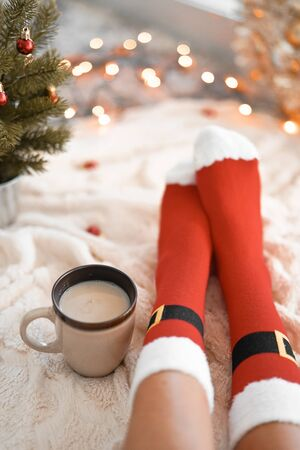 Feet in Santa's socks near the Christmas tree. Woman sitting at the blanket, drinks hot beverage and relaxes  warming up their feet in woollen socks. Winter and Christmas holidays concept Banco de Imagens - 137874895