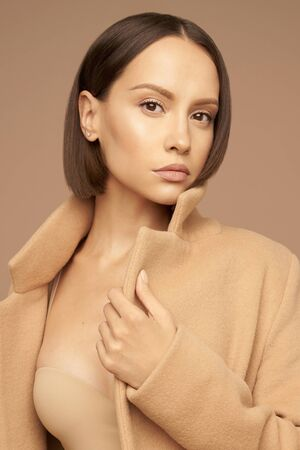 Fashion studio photo of young beautiful lady in beige coat on beige background. Total beige. Fashion look book. Warm Autumn. Warm Spring Imagens