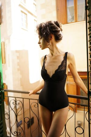 Lifestyle art photo of beautiful sensual brunette in black lingerie on the balcony. Beautiful morning