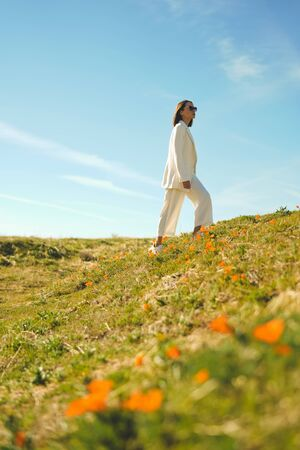 Outdoor lifestyle photo of beautiful young woman in white suit the poppy field. Freedom and independence Banco de Imagens