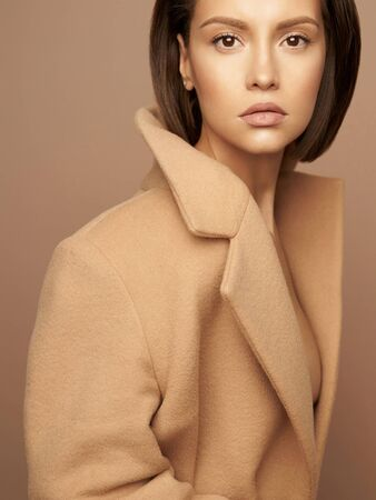 Fashion studio photo of young beautiful lady in beige coat on beige background. Total beige. Fashion look book. Warm Autumn. Warm Spring Banco de Imagens