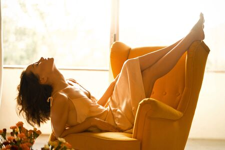 Fashion art photo of beautiful sensual woman in beige negligee in her boudoir. Home bedroom interior. Beautiful morning. Summer sunset