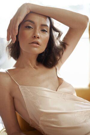 Fashion art portrait of beautiful sensual woman in beige negligee. Beautiful morning. Summer sunset Imagens