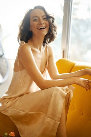Fashion art photo of beautiful cheerful woman in beige negligee in her bedroom. Beautiful morning. Summer sunset