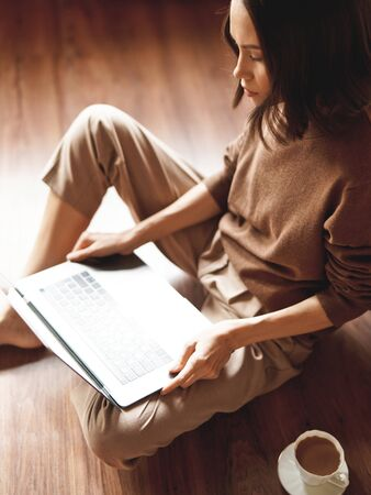 Lifestyle portrait of beautiful lady working at notebook sitting down on floor at home. Woman concept for alternative office freelance. Stay home